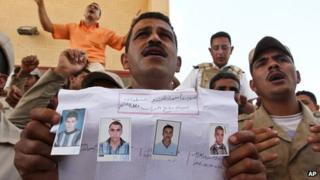 An Egyptian border policeman displays pictures of four of their colleagues who were kidnapped last Thursday, during a protest at the closed Rafah border crossing between Egypt and the Gaza strip, in Rafah, Egypt (20 May 2013)