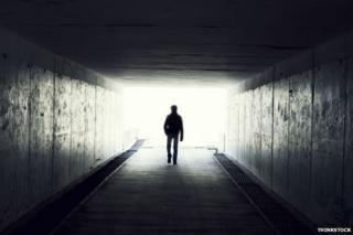 Man in tunnel walking towards light