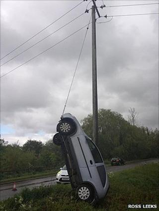 Car leaning against power cable on B1084 near Butley