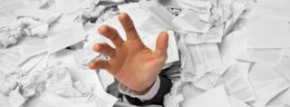 Hand reaching out from pile of paper
