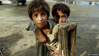An abandoned boy carries his disabled brother on his back in Karachi in 2003