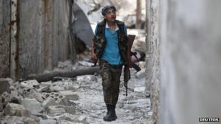 A member of the Free Syrian Army walks with his weapon in a damaged street filled with debris in Aleppo's Karm al-Jabal district on Monday