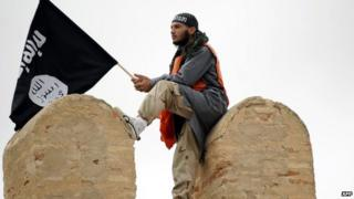 "A Tunisian Islamist waves a Salafist flag reading: ""There is only one God"" during a rally in May 2012 in Tunisia for the Ansar al-Sharia's national congress"