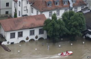 Rescue workers pass a flooded beer garden in Passau, Germany, 4 June
