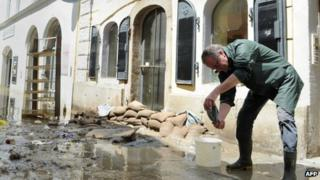 A resident cleans up his house in a street flooded by the river Danube in Passau, southern Germany, on June 5, 2013.