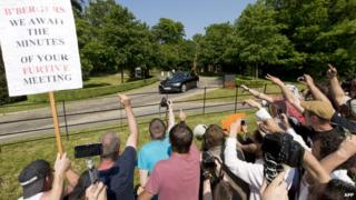 Protesters shout and wave a placard at the annual Bilderberg meeting in Watford, UK.