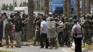 Lebanese soldiers and Hezbollah supporters are seen gathered in front of the Iranian embassy in Beirut