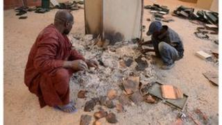 Men recover burnt ancient manuscripts at the Ahmed Baba Centre for Documentation and Research in Timbuktu, January 2013