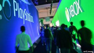 Attendees walk between signs for Sony PlayStation and Microsoft XBox on the first day of the Electronic Entertainment Expo (E3) in Los Angeles