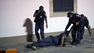 An policeman is dragged by his colleagues after being injured in Rio on 17 June 2013