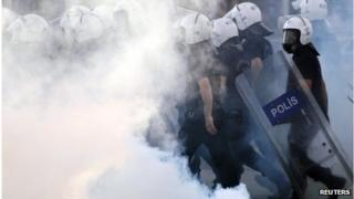 Police walk amidst tear gas during protests at Kizilay square in central Ankara, June 16, 2013