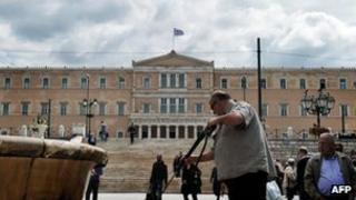 A municipal worker cleans the marble of a fountain in front of the Greek parliament in Athens