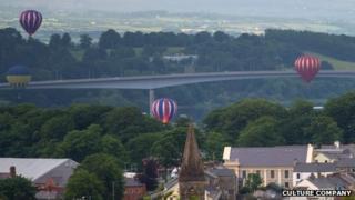 The balloons floatpast the Foyle Bridge