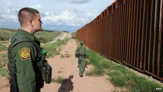 US Border Patrol agents Colleen Agle and Richard Funke patrol the border between Arizona and Mexico at the town of Nogales 28 July 2010