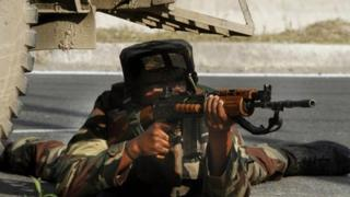 An Indian Army soldier takes position at the site of shootout on the outskirts of Srinagar, India, Monday, June 24, 2013