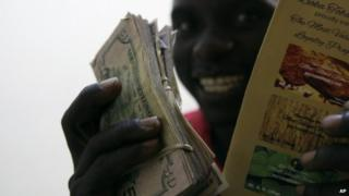 An tobacco farmer shows off his cash after selling his tobacco, at Boka Tobacco auction floors, in Harare, Zimbabwe, Tuesday 14 May 2013
