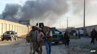 Afghan men carry a wounded man from a foreign logistics company as smoke rises from the entrance gate at the site of a suicide attack in Kabul on 2 July 2013