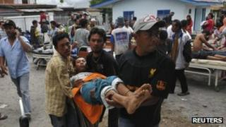 An injured resident is evacuated to the local clinic after a strong earthquake hit in Bener Meriah district in Central Aceh, Indonesia, 2 July 2013.