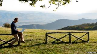 A man on his laptop in the countryside