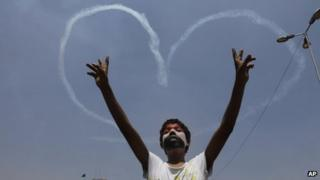 An Egyptian protester flashes v signs for military aircrafts forming a heart shape in the sky over Tahrir Square in Cairo, Egypt,, July 5, 2013.