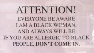 Sign which says 'attention, everyone be aware I am a black woman'