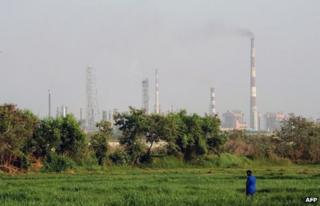 In this photograph taken on April 22, 2013, an Indian man stands in a field as factory chimneys from an industrial area loom in the background in Mumbai.