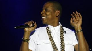 Jay Z holding a microphone and smiling.