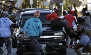 People jump on a car on Crenshaw Boulevard during a protest against the acquittal of George Zimmerman in the Trayvon Martin case in Los Angeles on 15 July 2013