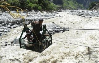 A local man throws a rope as he and others riding a gondola cross the Alaknanda river from the Hemkund Sikh temple to Govindghat following flash floods in Uttarkhand state on June 30, 2013