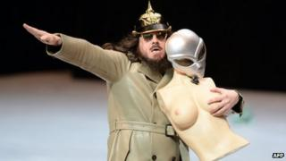 German artist Jonathan Meese gives a Nazi salute while performing 'Generaltanz den Erzschiller' on stage at the National Theatre in Mannheim, western Germany, on 26 June, 2013
