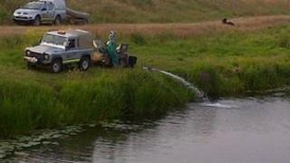 Environment Agency staff treating the river at Welney in Norfolk