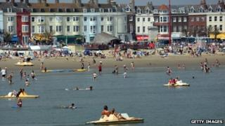 People enjoy the beach on 22 July in Weymouth, England
