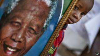 A young boy poses for a photograph of him holding a portrait of Nelson Mandela next to a wall of get-well messages and flowers laid outside the Mediclinic Heart Hospital where former South African President Nelson Mandela is being treated in Pretoria, South Africa Monday, July 8, 2013.
