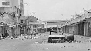 An abandoned burnt out automobile and street filled with rubble, Colombo, July 30 1983