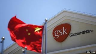 Chinese national flag flutters in front of a GlaxoSmithKline office building in Shanghai