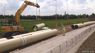Crane lifting long pipe