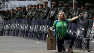 Pilgrim poses in front of riot police in Rio de Janeiro