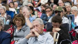 Mourners watch a memorial service on screen outside Saint Agnes church in Lac Megantic on 27 July, 2013, three weeks after a runaway oil train derailed and exploded in the town, killing 47 people
