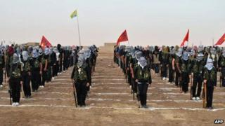 Kurdish opposition fighters attend a ceremony on 18 July 2013, in the northern Syrian border village of Qamishli