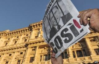 A person holds up a poster portraying Silvio Berlusconi behind bars in Rome, 1 August