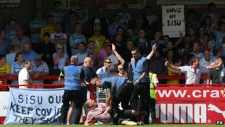 Stewards wrestling one of the protesting Coventry fans to the ground