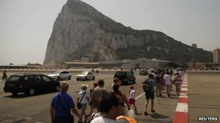Pedestrians and drivers cross the tarmac of the Gibraltar International airport in front of the Rock of the British Colony of Gibraltar on 4 August