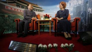Flowers are laid in front of a wax statue of Margaret Thatcher at an exhibition centre in Shenzhen, China, following her death