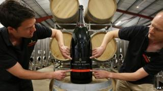 Assistant winemaker Josh Donaghay-Spire (left) and winemaker Andrew Parley fix the label to the Nebuchadnezzar bottle