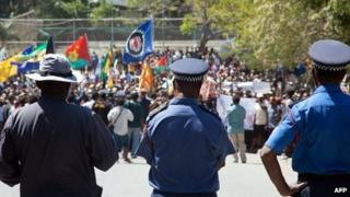 Papua New Guinea police officers watch as hundreds of students march towards the university gate in Port Moresby on 2 August 2013, during a protest rally against Australia and PNG's asylum seeker plan
