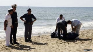 Italian police recover a body from La Playa beach in Catania, Italy, 10 August 2013