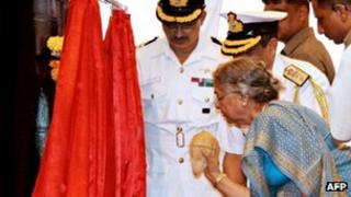 Gursharan Kaur, the wife of Indian Prime Minister Manmohan Singh, breaks a coconut on the hull of India's first nuclear-powered submarine INS Arihant in 2009