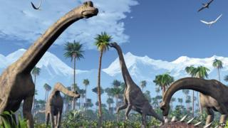 Artwork of four Brachiosaurus dinosaurs feeding in a forest of tree ferns next to snow-capped mountains
