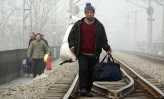 A Chinese migrant worker walking with his baggage along a railway line in Beijing.