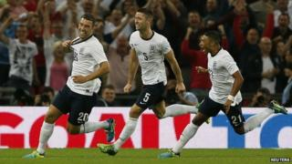 England's Lambert celebrates scoring against Scotland with teammates Cahill and Oxlade-Chamberlain
